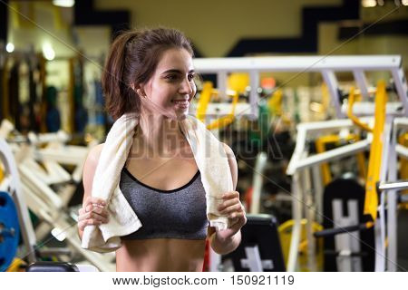 Beautiful young sporty woman. Fitness girl training in sport club with exercise equipments. Woman smiling and looking at camera