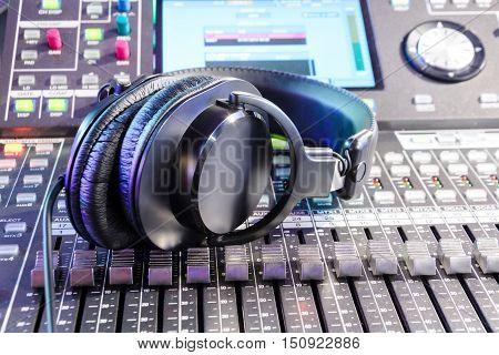 Studio headphones lying on top of the mixing console. Sound mixer. Live and studio equipment