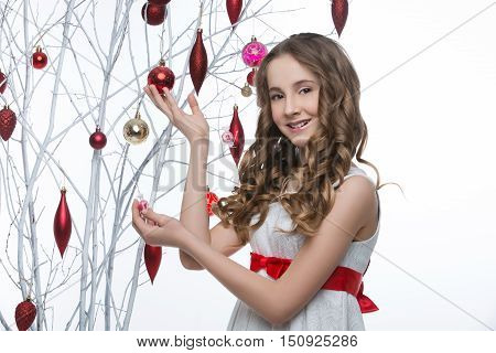 Beautiful teen girl with long curly hair in white dress with red ribbon belt standing near white tree branches wiht christmas decorations hanging on it. Studio shot on white background. Copy space.