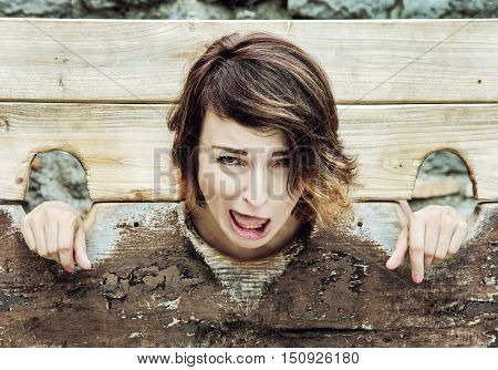 Young caucasian brunette woman in medieval pillory. Negative emotions. Misery theme. Punishment device.