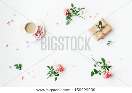 Workspace. Gift cup of coffee and rose flowers. Flat lay top view
