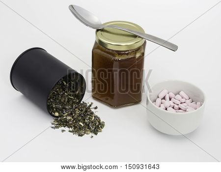 Dried herbs making a green herb tulse with chestnut honey and Vitamin B12 tablets