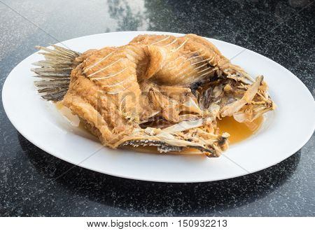 Fried fish with fish sauce in white dish.