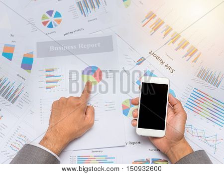 Businessman poiting at financial sheet paper on the table while hodling blank smartphone mobile