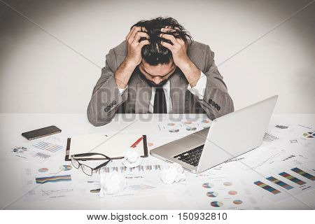 Portrait of stressed businessman burnout holding his head with both hand at work