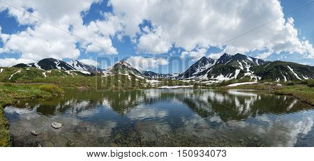 Beautiful landscape of Kamchatka Peninsula: summer panoramic view of Mountain Range Vachkazhets, mountain lake and clouds in blue sky on sunny day. Eurasia, Russian Far East, Kamchatska Region.