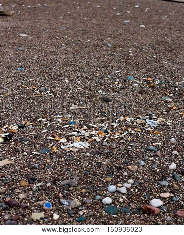 Many cigarette butts and other debris on the beach after surf