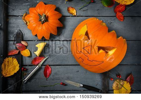 Preparing a carved pumpkin for halloween autumn decoration tinkering on a gray rustic wooden table selected focus