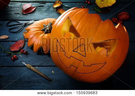 Carving a pumpkin for halloween tinker autumn decoration on a blue rustic wooden table selected focus narrow depth of field