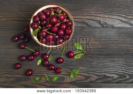 Red ripe cherries in bowl ceramic red cherries on wooden table green cherry leaves brown wooden background top view