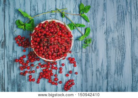 Ripe red currant berries in white bowl redcurrants on blue wooden table sprigs of mint red currant on branches top view