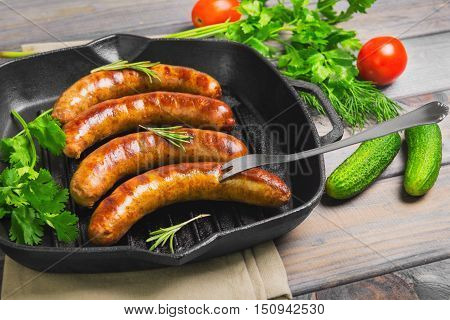 Grilled fried sausages kupaty on a cast iron skillet grill greens to grilled fried sausages parsley thyme rosemary vegetables tomatoes cucumbers. Fork for fried sausages. Grey wooden background.
