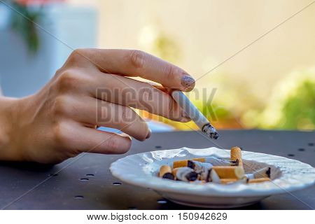 smoking cigarette - woman's hand holding a cigarette over the ashtray full of burnt cigarettes close up view - concept of unhealthy nicotine addiction
