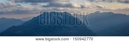 Panorama of mountains in light of evening sun. Greater Caucasus Mountain Range. Caucasus mountains. Karachay-Cherkessia. Russia.