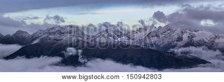 Snow-covered top of Greater Caucasus Mountain Range in morning twilight. Caucasus mountains. Karachay-Cherkessia. Russia.