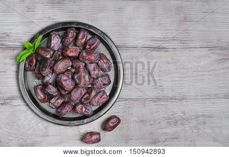 Side view of metal plate of Tunisian pitted dates mint. Dried dates on wooden white table top background. Top view.