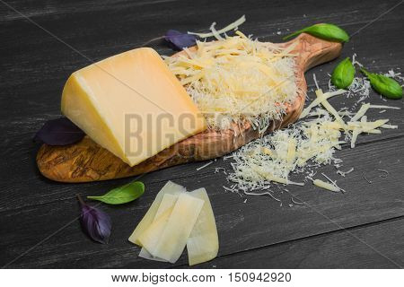 Parmesan cheese piece on wooden board olive wood. Parmesan cheese thin slices on the table. Parmesan cheese grated. The dark black background. The leaves of spinach basil.