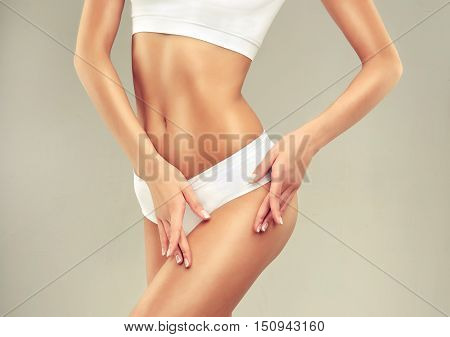Perfect slim toned young body of the girl . An example of sports , fitness or plastic surgery and aesthetic cosmetology.  Model woman shows the hip  and thigh  without cellulite