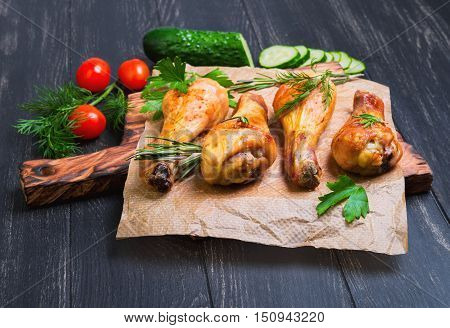 Chicken with vegetables. On cutting board grilled chicken drumstick meat ingredients for chicken drumsticks parsley dill rosemary cherry tomatoes cucumber black dark wood background