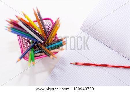 The colored new pencils and empy copybook