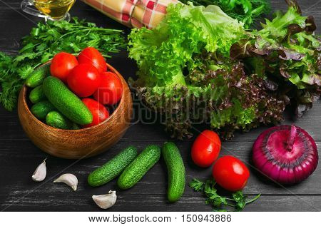Vegetable Ingredients for cooking vegetable salad cloth. Vegetables cucumber cherry tomatoes purple onion garlic cloves parsley dill lettuce salad leaves vegetable oil Dark black wooden background