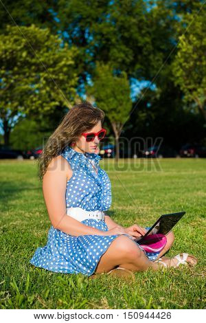 Young woman with red sunglasses and dress sitting in grass outside typing on small netbook
