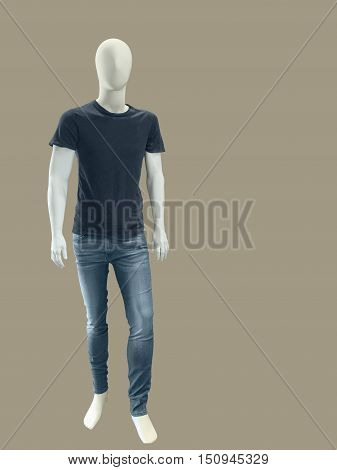 Full length male mannequin dressed in t-shirt and jeans isolated on brown background. No brand names or copyright objects.