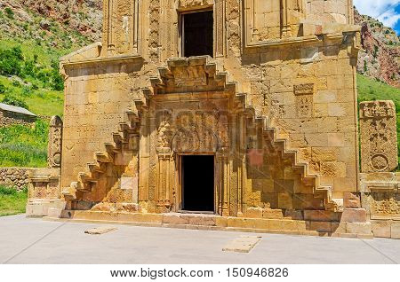 The Surb Astvatsatsin (Burtelashen) Church of Noravank Monastery decorated with tympanium reliefs of Mother of God with Archangels Gabriel and Michael decorative stairs and surrounded by khachkars Vayots Dzor Armenia.