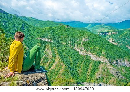 The young man sits on the rock over the precipice and watches the heavy rainy clouds lying on the green mountains of Vorotan Canyon Halidzor Syunik Province Armenia.