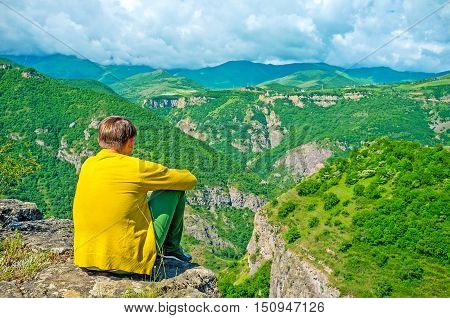 The lonely young man sits over the precipice and enjoys the nature of Syunik Province Halidzor Armenia.