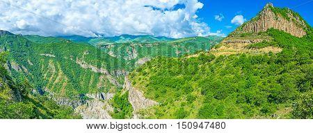 The Vorotan river gorge with the massive basalt outputs lush greenery on the steep slopes and medieval Tatev Monastery on the distance Halidzor Syunik Province Armenia.
