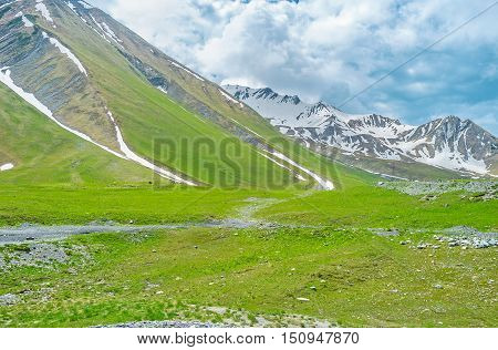 Even in summer the mountains of Greater Caucasus are covered with snowfields and clouds Gudauri Georgia.