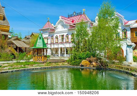 The tiny garden with a pond among the mansions museums and workshops of Izmailovsky Kremlin the Russian style cultural art and entertainment center Moscow Russia.