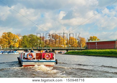 ST PETERSBURG RUSSIA-OCTOBER 3 2016. Ioannovsky or St John bridge and sailboat floating on the Kronverk strait in St Petersburg Russia. Architecture landmark of St Petersburg in autumn sunny weather