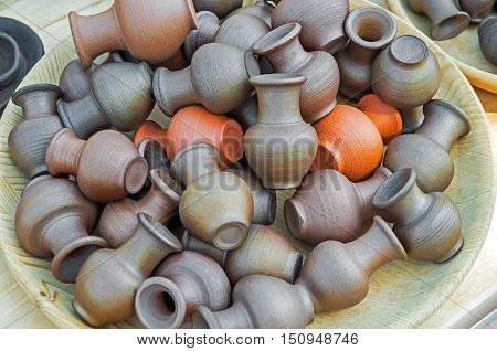 Wooden bowl with a handful of small clay pots and jugs
