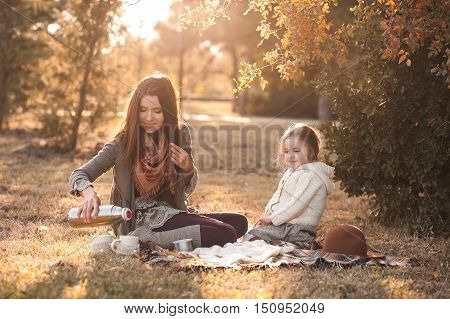 Smiling mother 20-24 year old and kid daughter 4-5 year old have picnic with hot tea outdoors. Motherhood. Family time.