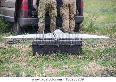 Military drone with propeller on army box on background of male legs in uniform