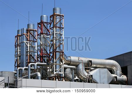 Ventilation pipes and actuators on the roof of an industrial building