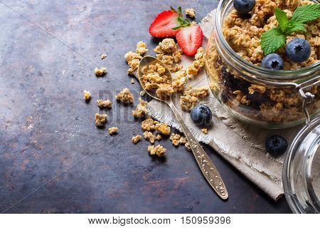 Breakfast, healthy food concept. Homemade muesli granola with berries in a jar on rusty black table. Selective focus, copy space background