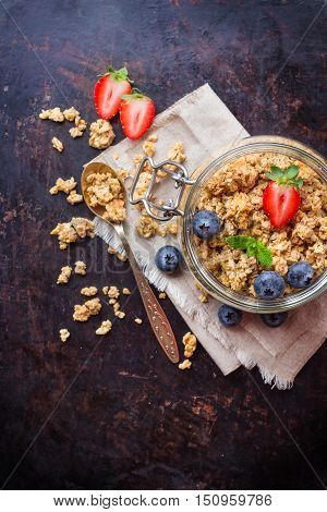 Breakfast, healthy food concept. Homemade muesli granola with berries in a jar on rusty black table. Selective focus, copy space background, top view flat lay overhead