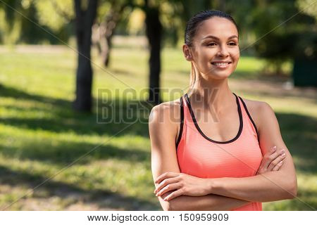 Happy to move. Delighted young beautiful girl wearing a sportswear and posing in the park after having morning exercises.