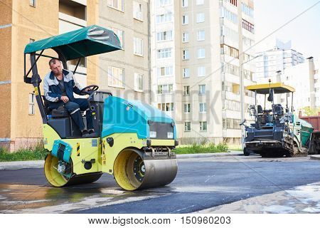 Road construction. Worker on steam vibration roller compacting asphalt
