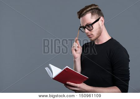 Time to organize your schedule. Wistful bearded young man wearing glasses and holding pencil and notebook while standing against grey background