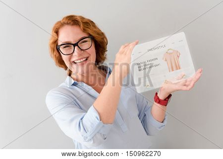 Clearance sale. Overjoyed positive adult woman smiling and holding tablet while standing isolted on grey background