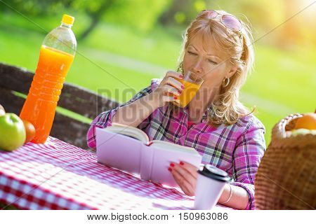 Relaxing in nature.Mid adult woman sitting in park and reading a book on picnic.