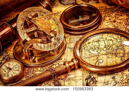 Vintage still life. Vintage magnifying glass lies on an ancient world map in 1565.