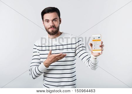 Surprising technologies. Puzzled young bearded man holding the digital gadget while being isolated on white background