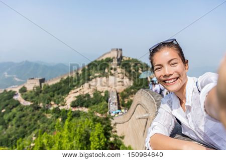 Selfie. Tourist at Great Wall of China excited and happy having fun at famous Badaling during travel holidays at Chinese tourist destination. Woman tourist taking picture during Asia vacation.