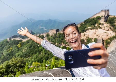 Great Wall of China. Tourist taking selfie photo at famous Badaling during travel holidays at Chinese tourist destination. Woman tourist taking picture using smart phone during Asia vacation.