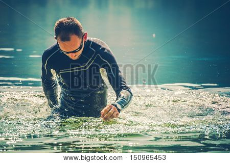Wetsuit Water Sports. Caucasian Sportsman in the Black Wetsuit.